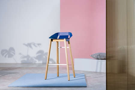 Real photo of an art gallery interior with a blue bar stool with wooden legs on display against pastel pink wall