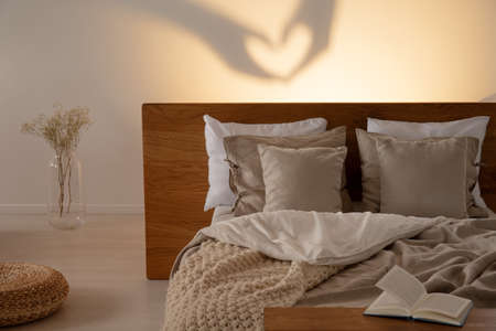 Heart shaped shadow in a bedroom interior with a comfy bed with pillows and blanket. Real photo