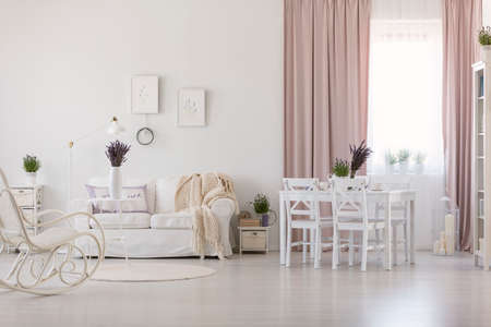 White chairs at dining table in apartment interior with blanket on sofa and pink drapes. Real photo Standard-Bild - 106805985