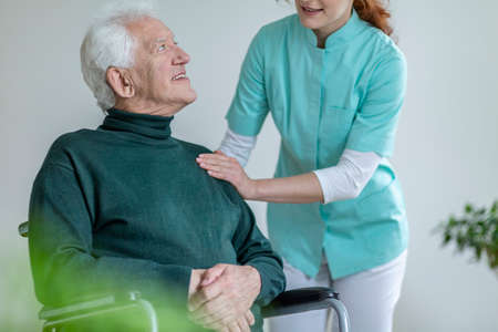Caregiver talking to a happy man in a wheelchair in a nursing house