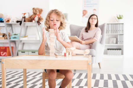 Wooden development props in the hands of a child during an educational therapy meeting with a pedagogue in a private medical office.