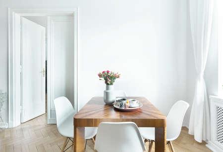 Eettafel met verse bloemen en ontbijt dienblad met koffiekopje en fruit in echte foto van witte kamer interieur met lege muur. Plak hier je schilderij