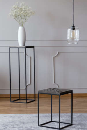 Metal end table standing on carpet in real photo of bright room interior with glass lamp, wainscoting on wall and flowers in vase placed on stand in blurred background