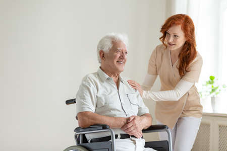Friendly nurse supporting smiling paralyzed senior man in a wheelchair Stock Photo