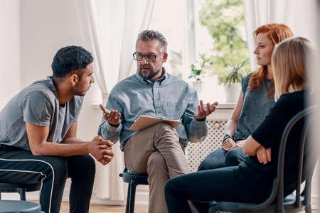 Consejero hablando con un grupo de adolescentes rebeldes con depresión