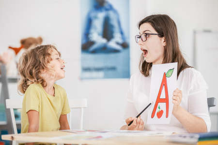 Speech therapist working with a child on a correct pronunciation using a prop with a letter a picture.