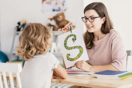 A child with development problems with a professional speech therapist during a meeting. Tutor holding a prop poster of a snake as a letter 's'.