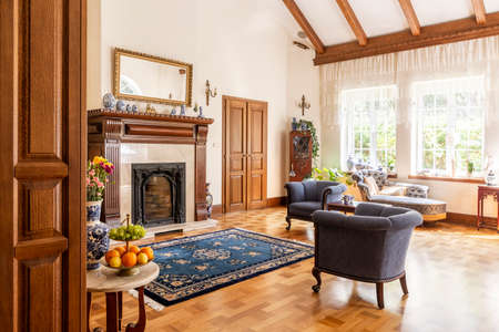 Blue armchairs and patterned carpet in front of wooden fireplace in sophisticated interior. Real photo Imagens