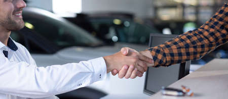 Panorama of smiling car dealer shaking hand with buyer in the salon Stockfoto