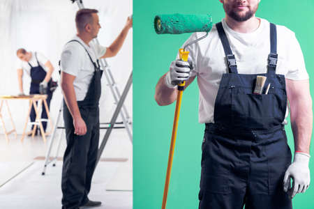 Wall painter in dungarees holding a paint roller on a neo mint green wall background and home interior renovation crew in the background