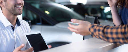 Panorama of mockup of tablet of smiling car seller during transaction