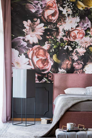 Flowers print on the wall in feminine bedroom interior with grey sheets on pink bed. Real photo