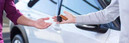 Panorama y primer plano de la mano del vendedor de automóviles con llaves y la mano del comprador después de la transacción