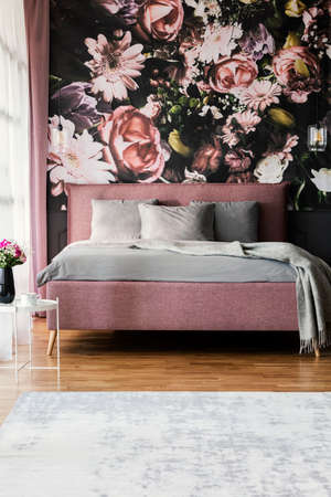 Flowers wallpaper in feminine pink bedroom interior with grey pillows on bed. Real photo