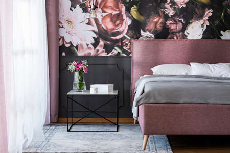 Flowers on table next to pink bed with grey sheets in bedroom interior with wallpaper. Real photo