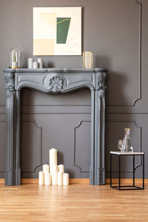 Candles under fireplace portal in grey living room interior with poster and table. Real photo Stock Photo