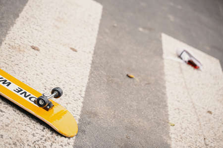 Kid's skateboard on pedestrian crossing after dangerous traffic incident 免版税图像