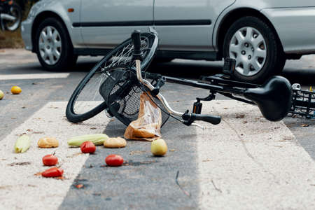 Groceries and broken bike on pedestrian crossing after collision with a car 版權商用圖片