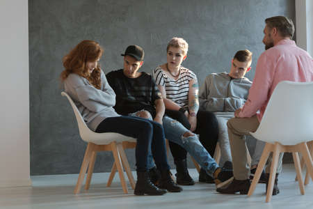 A group of teenagers looking at a withdrawn, lacking self-esteem young girl during a psychotherapy session with a coach. Stock Photo