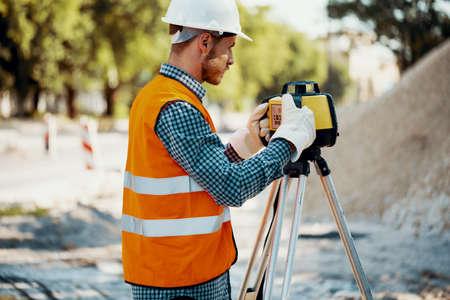 Engineer in reflective vest and white helmet using geodetic equipment