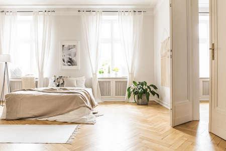 Geräumiges und helles Schlafzimmer mit beigen Verzierungen, Holzboden und einem Buch auf der Fensterbank Standard-Bild