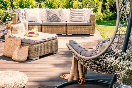 Pillows on rattan couch near table on patio with hanging chair in the garden. Real photo 版權商用圖片