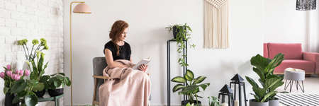 Young woman covered with blanket sitting on armchair and reading a book in white apartment interior with many fresh plants