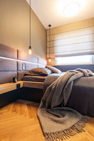 Blanket on bed under lamps in hotel bedroom interior with window and wooden floor. Real photo Stock Photo