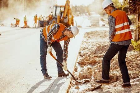 Arbeiter in Warnwesten mit Schaufeln während der Fahrbahnarbeit