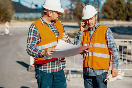 Worker and construction manager consulting on a project with engineer during road work
