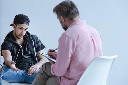 Vista posterior de un especialista en psicología hablando con un joven rebelde (vista frontal) con problemas de violencia y drogas durante una sesión de asesoramiento individual. Foto de archivo