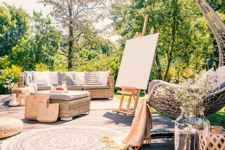Mockup of easel on terrace in the garden with rattan table and sofa during summer. Real photo 스톡 콘텐츠