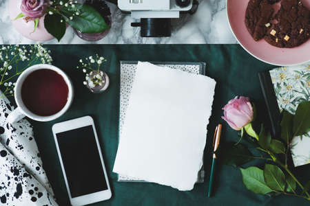 Top view on mockup of paper and smartphone on table with pink roses and cup of coffee