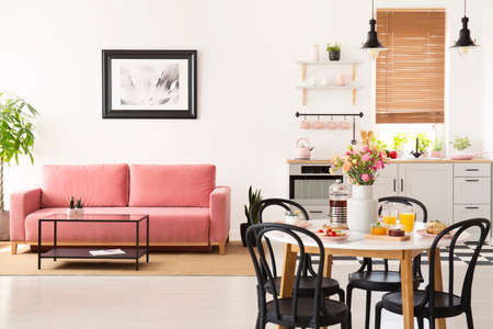 Dining table with breakfast and fresh flowers standing in bright apartment interior with pink sofa, black and white poster and kitchenette with pastel accessories Stok Fotoğraf - 107018487