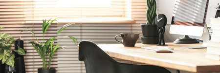 Coffee cup, creative clock and a desktop computer on a wooden desk in a sunny workspace interior with plants Reklamní fotografie