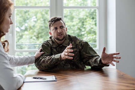 Soldier talking about his war experience with fear. Psychiatrist showing support Stok Fotoğraf