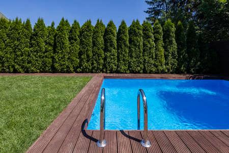 Zwembad in de tuin met bomen en groen gras tijdens de zomer. Echte foto Stockfoto