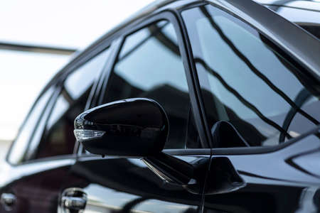 Close-up of a side mirror of a black family car for sale at a modern dealership