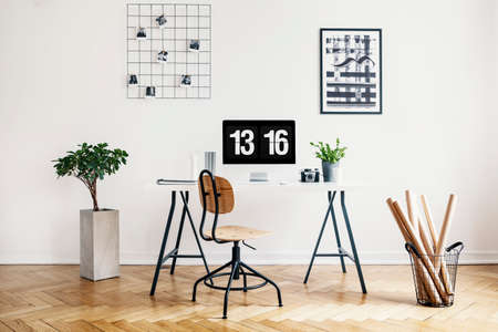 Real photo of a simple home office interior with a desk, chair, plant, computer, poster and wall organizer Stock Photo