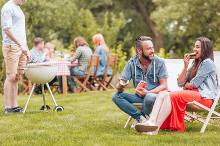 Young woman and man sitting on deck chairs and talking during garden grill party. Other people sitting by a table in the blurred background.