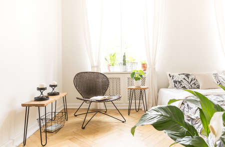 Bright light shining through a window into a modern bedroom interior with a rattan and metal chair, bedside stand with candles and a bed. Copy space on white wall. Real photo. Stock Photo