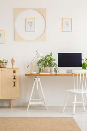 White chair at desk with desktop computer in workspace interior with plants. Real photo