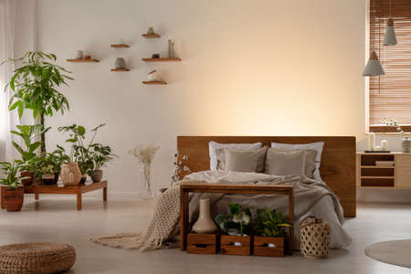 Plants and pouf in dark bedroom interior with light behind wooden bed with headboard. Real photo