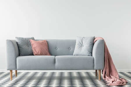 Pink blanket on grey couch with pillows on checkered floor in white living room interior. Real photo
