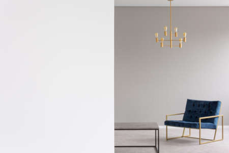 Copy space on white empty wall in flat interior with gold chandelier above blue armchair in blurred background. Real photo with a place for your light switch