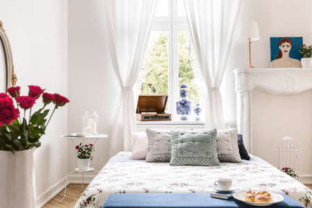 Drapes at window above bed with cushions in white bedroom interior with poster and roses. Real photo Stockfoto