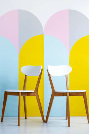 Two chairs set on a patterned wall with yellow accents in bright office interior. Real photo Archivio Fotografico