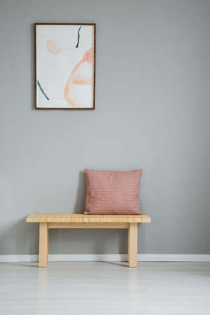 Poster on grey wall above wooden bench with pink pillow in simple apartment interior. Real photo