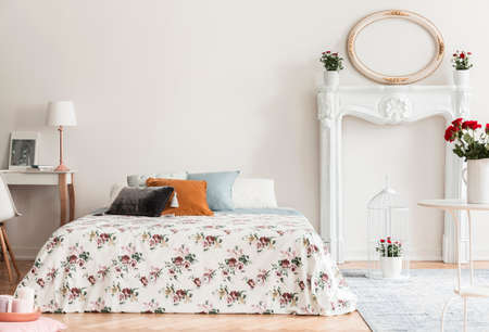Lamp on desk next to patterned bed with pillows in white bedroom interior with mirror. Real photo