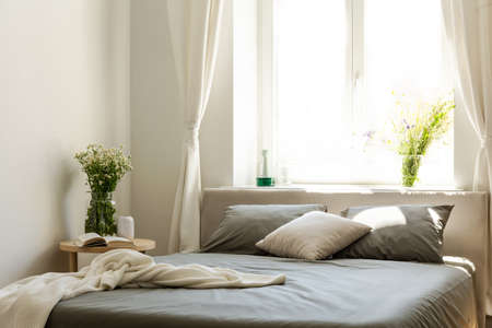 Blanket and pillows on grey bed in bright bedroom interior with flowers and window. Real photo